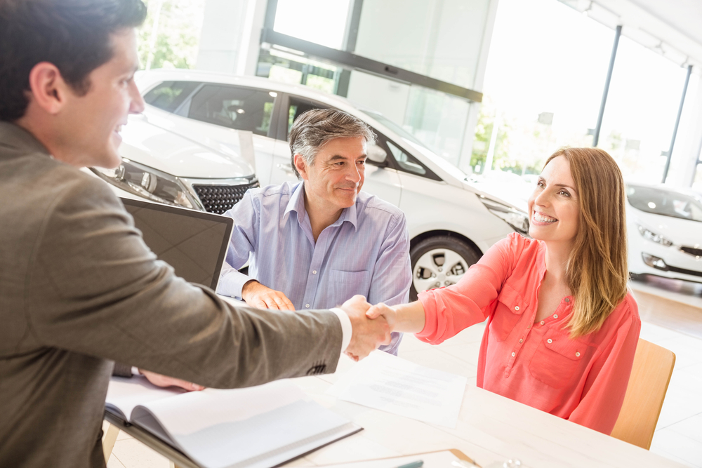 couple shaking hands with salesperson at car dealership