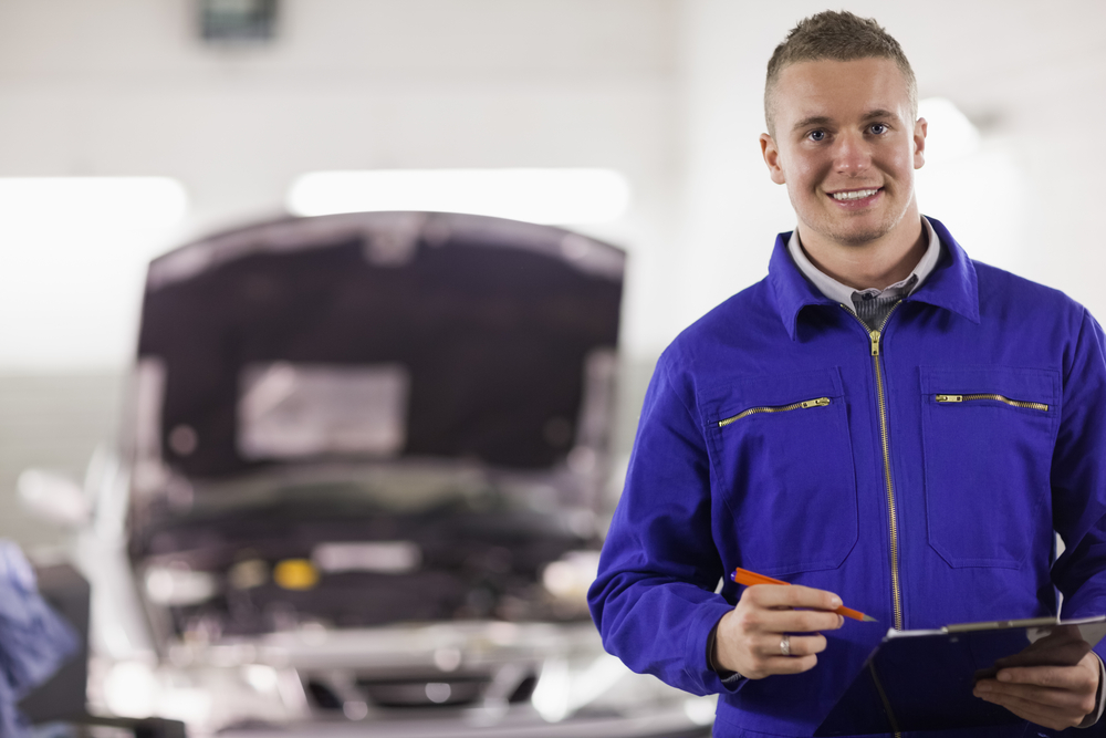 Mechanic holding a clipboard and a pen next to a car in a garage