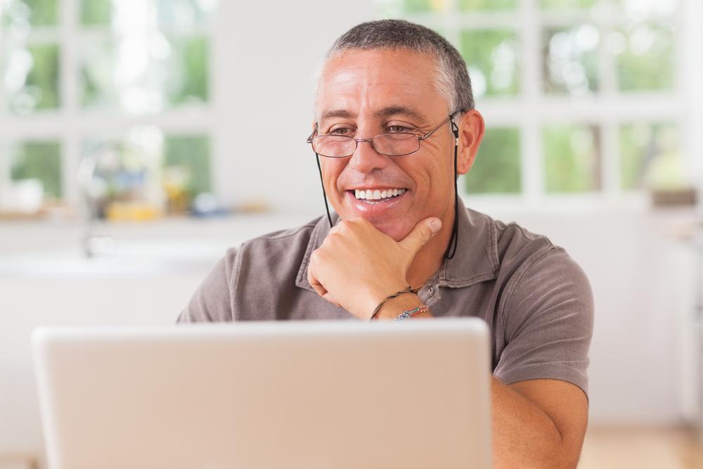 Smiling man at laptop in kitchen