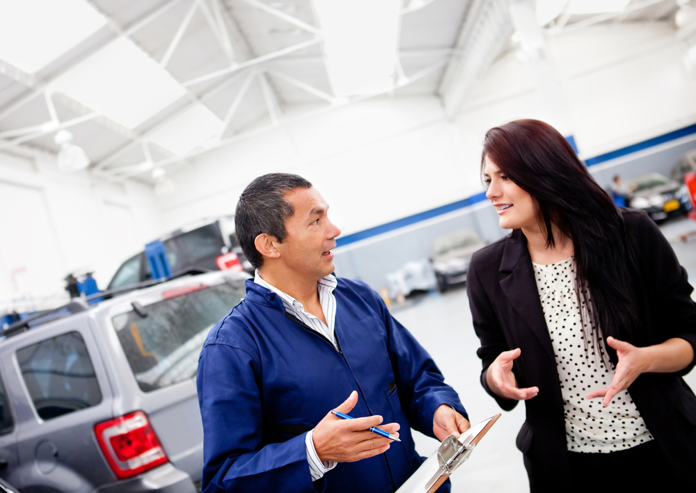 Mechanic explaining to a woman what happened to her car