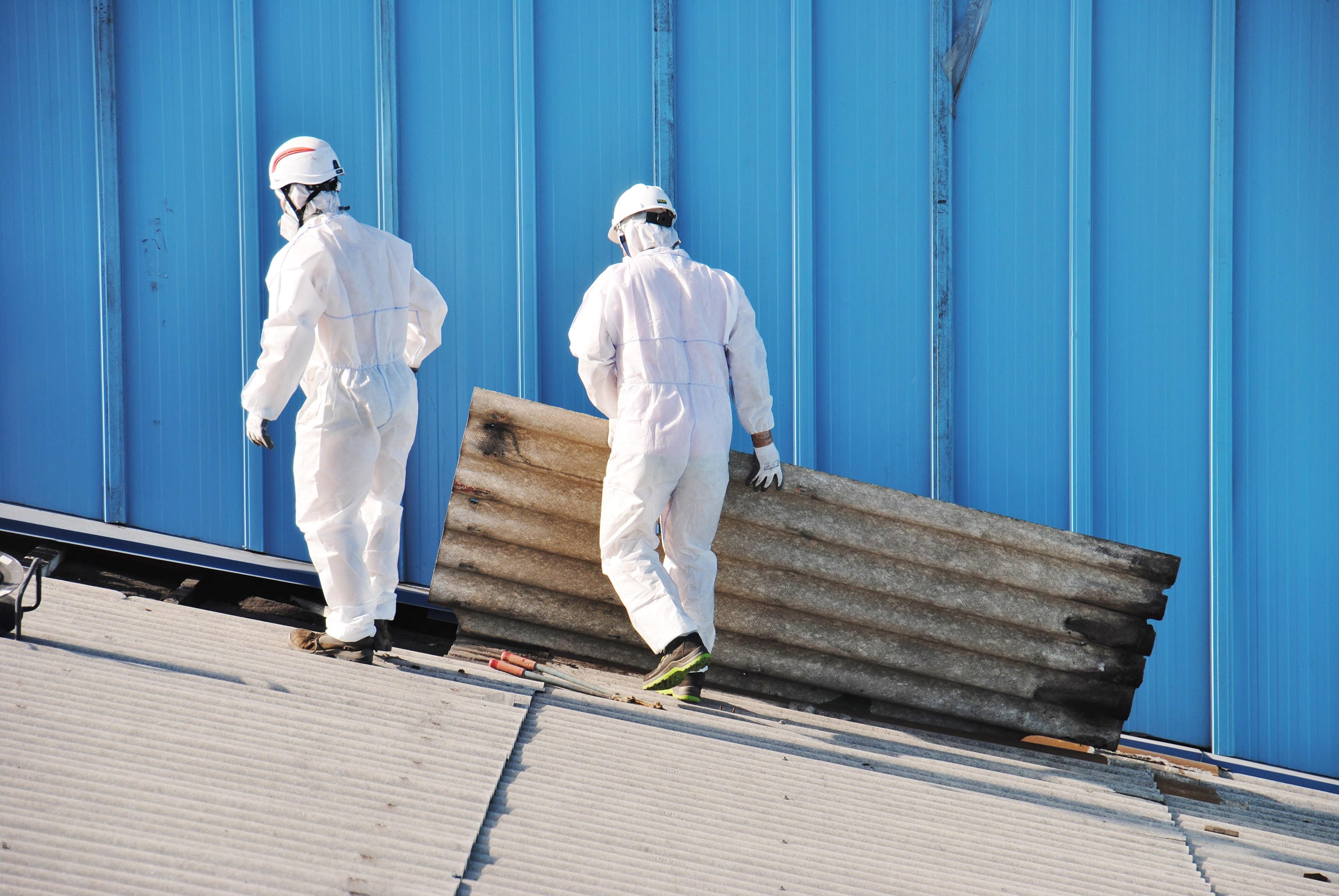 intervention de deux techniciens en tenue de protection pour constater la présence d'amiante