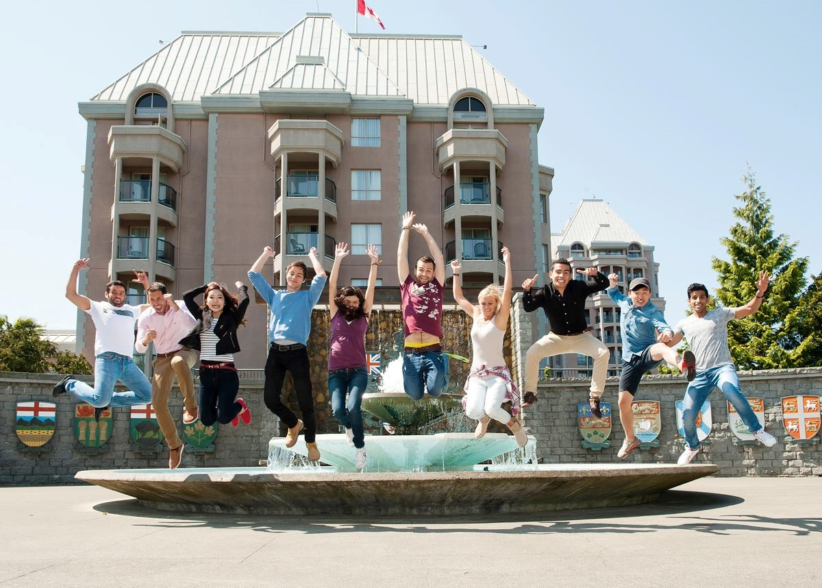 International students from Global Village Victoria jump in front of Confederation fountain in Confederation Garden Court